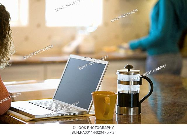 Young woman drinking coffee and working on her laptop in the morning