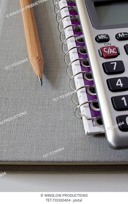Calculator, textbook and pencil on notebook, studio shot