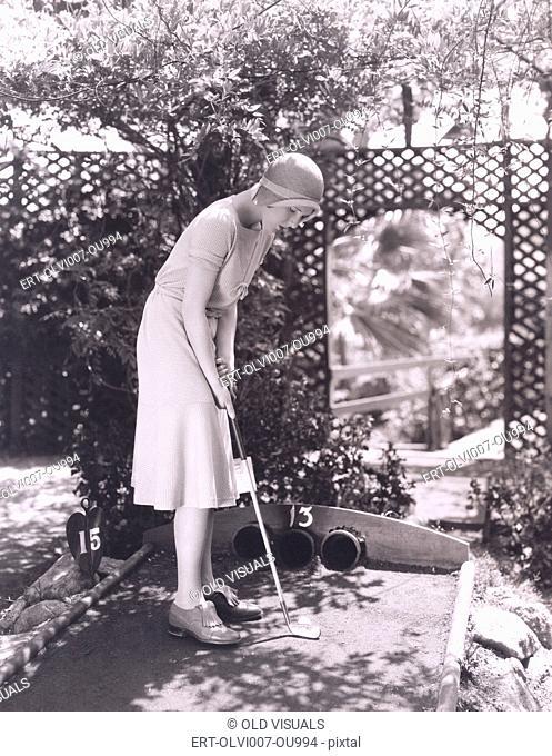 Woman playing miniature golf (OLVI007-OU994-F)
