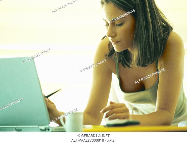 Woman leaning on table using laptop
