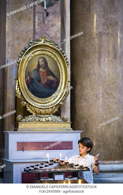 Boy light a votive candle in front of a picture of Jesus, Rome, Italy