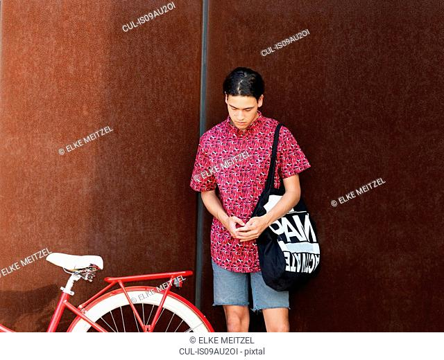 Young man standing beside bicycle