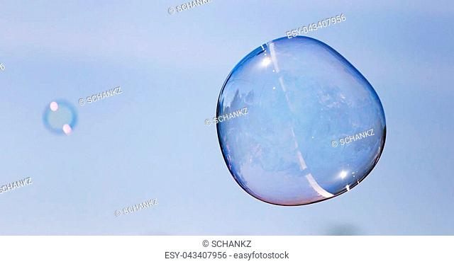 Big soap bubble against the blue sky