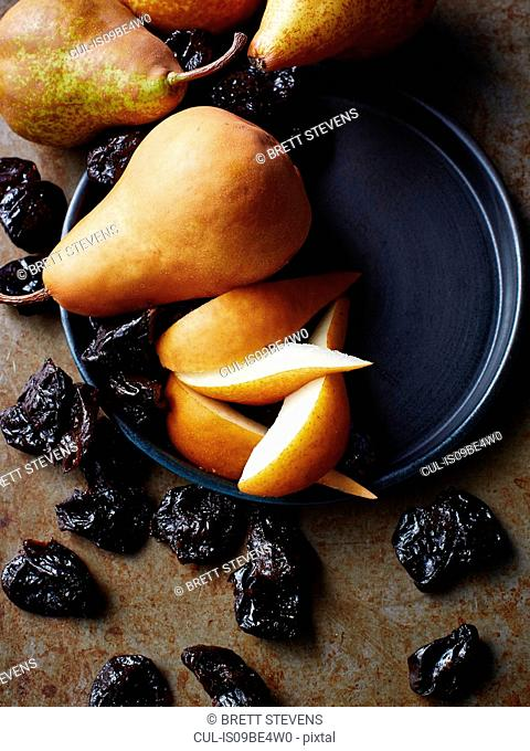 Still life with fresh pears and prunes, overhead view