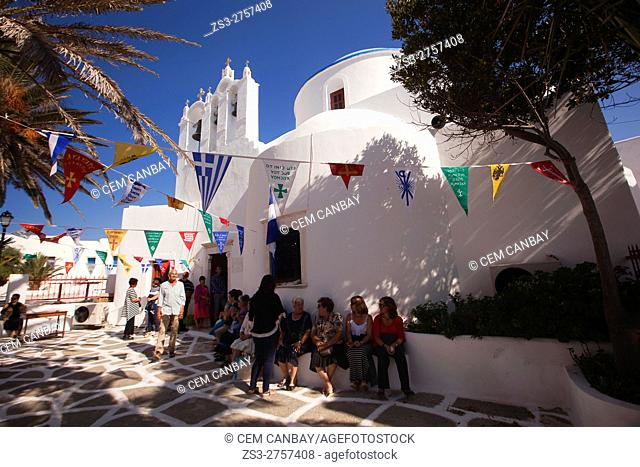 Local people sitting in front of the blue domed church during a celebration in the Kastro or Castle area, Sikinos, Cyclades Islands, Greek Islands, Greece