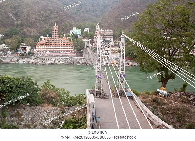 High angle view of a suspension bridge across a river with Trayambakeswar temple in the background, Lakshman Jhula, Rishikesh, Dehradun District, Uttarakhand