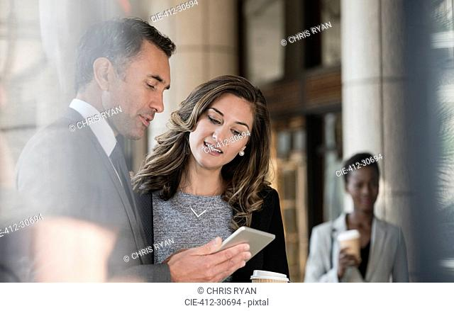 Corporate businessman and businesswoman using digital tablet