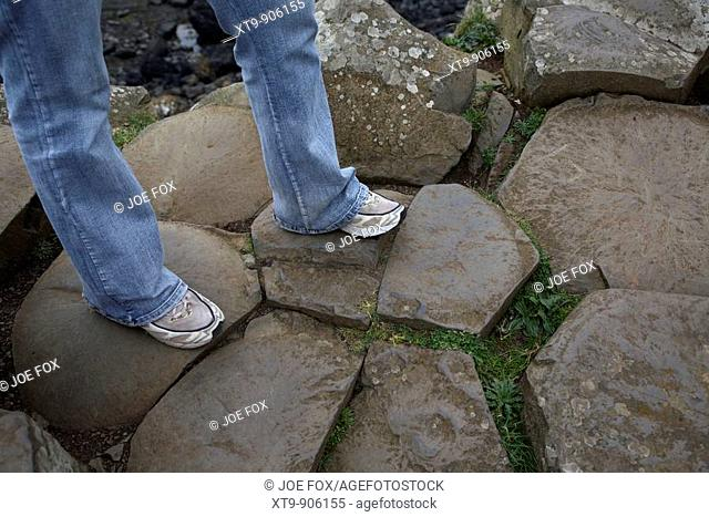 womans legs wearing jeans and old trainers on red basalt hexagonal rock formations at the giants causeway county antrim northern ireland uk