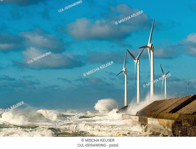 Stormy ocean waves splashing wind turbines on harbour wall, Boulogne-sur-Mer, Pas de Calais, France