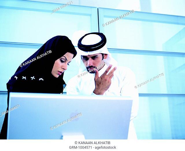 Arab businesspeople working on computer