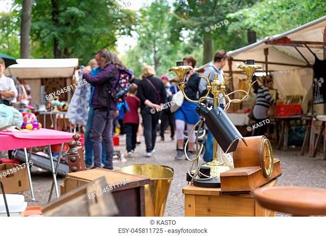 Market boot with objects beeing selled at the weekend flea market in Berlin city center. Out of focus curious visitors in the background