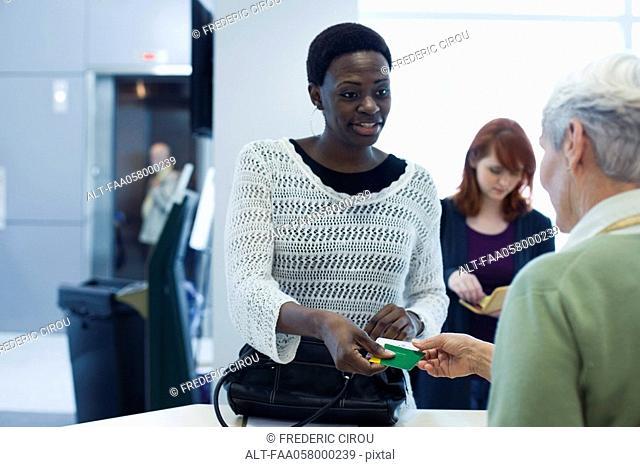 Female customer handing credit card to cashier