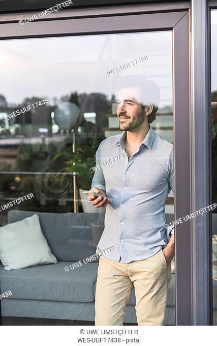 Young man looking out of window, using smartphone