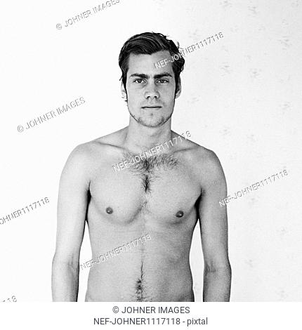 Young shirtless man standing in front of wall