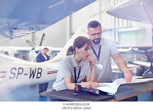 Airplane mechanics reviewing plans in hangar