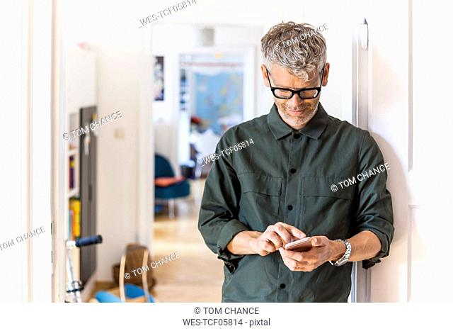 Mature man leaning against door case at home using cell phone