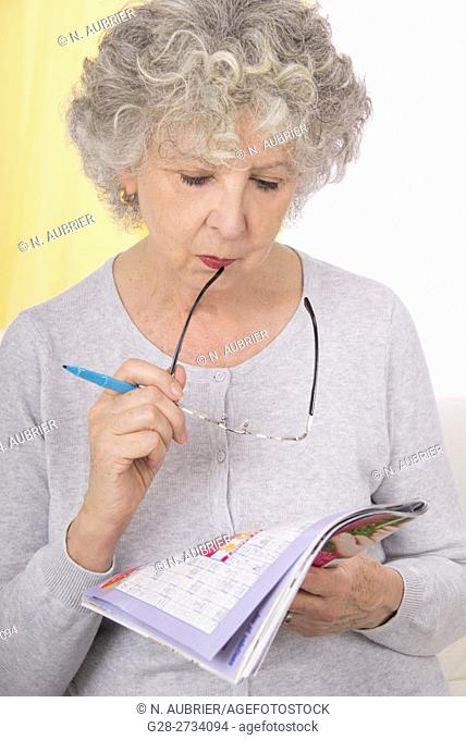 Senior woman sitting on her sofa, thoughtful and peacefully making crosswords, her spectacles in her mouth