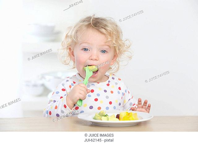 Baby eating fruit with fork