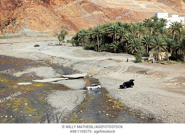 car stuck in river runlet in wadi with date palms at the village of Fanja, Hajar al Gharbi, Sultanate of Oman, Asia