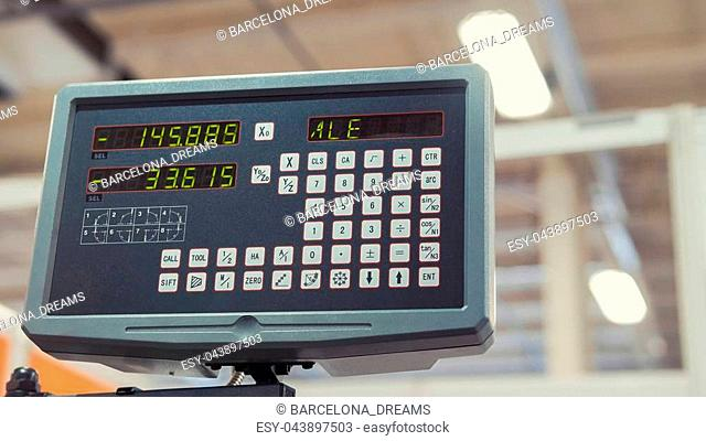 LCD remote control for machine at industrial manufacture factory, close up