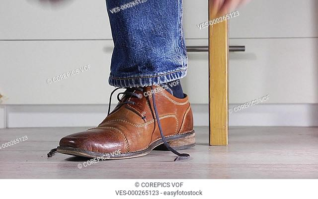 Close up of a man wearing jeans tying the shoe laces of his brown leather shoe