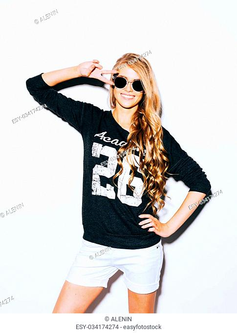 Happy Young Woman Showing Victory Sign in Sunglasses On White Background. Indoor. Warm color. Hipster