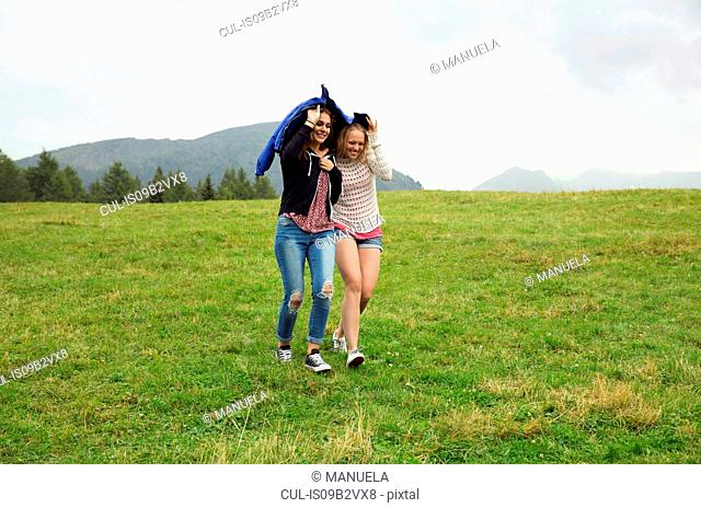 Two young women running down hill holding up anorak in rain, Sattelbergalm, Tyrol, Austria