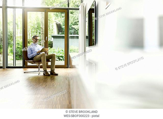 Man sitting on chair in his living room using tablet