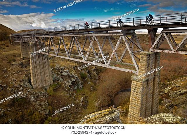 Cyclists cross old bridge on Otago Rail Trail near Oturehua, Central Otago, New Zealand