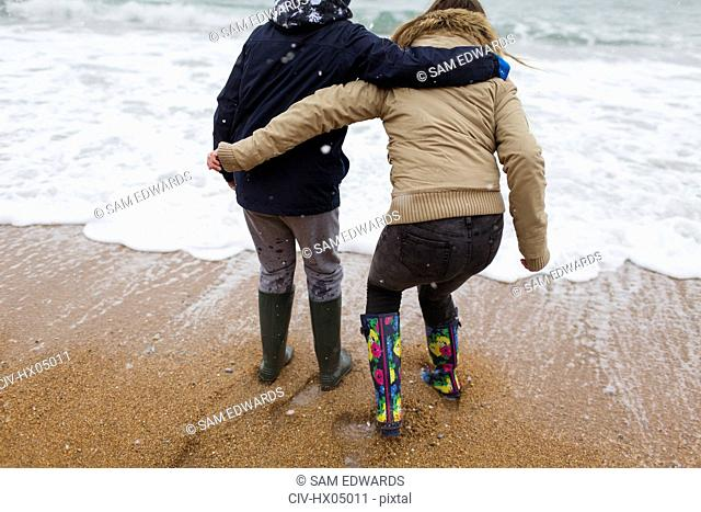 Playful teenage brother and sister playing in winter ocean surf