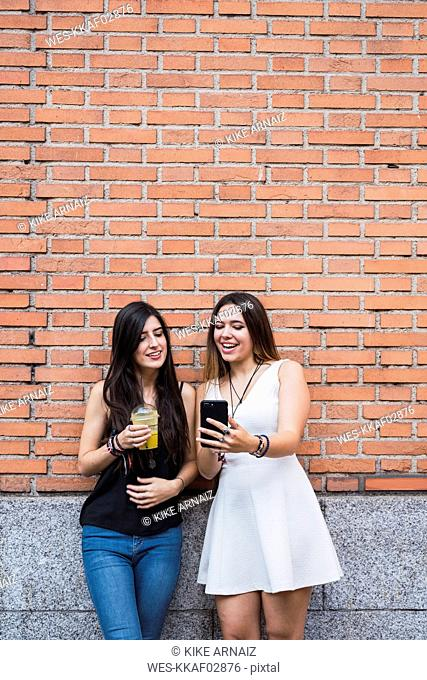 Girl frinds standing in front of a brick wall, looking at smartphone