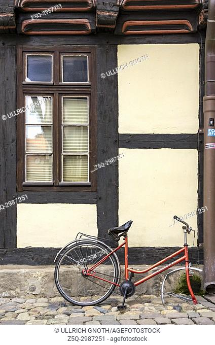 Broken and abandoned bicycle in front of historic half-timbered architecture in Hoelle Alley in the Old Town of Quedlinburg, Saxony-Anhalt, Germany