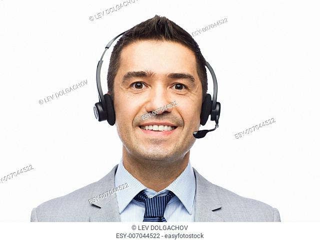 business, people, technology and service concept - smiling businessman in headset
