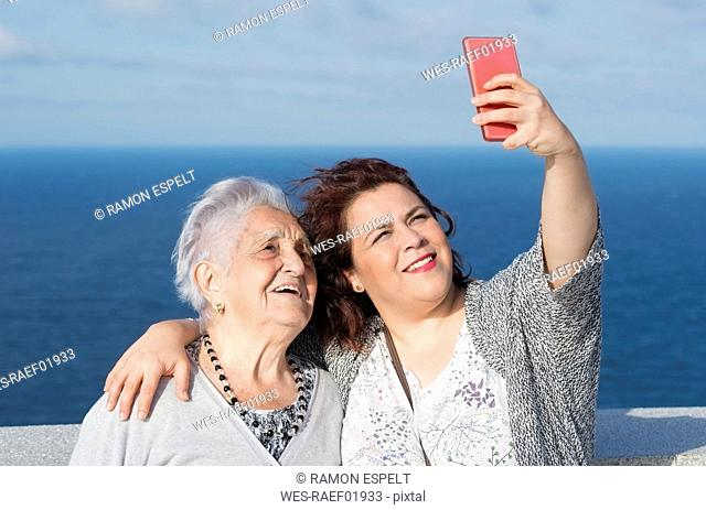 Grandmother and granddaughter taking a selfie in front of the sea
