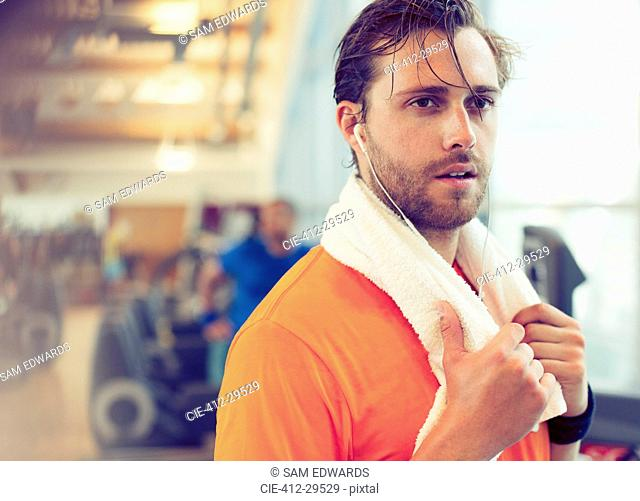 Sweating man with towel and headphones resting in gym