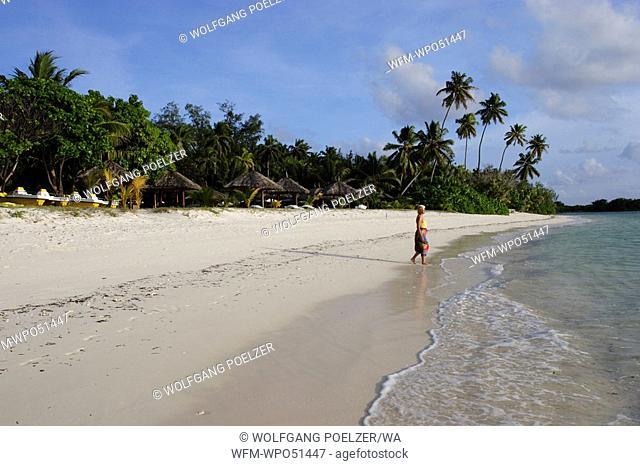 woman walking on tropical beach, Desroches Island Indian Ocean, Seychelles