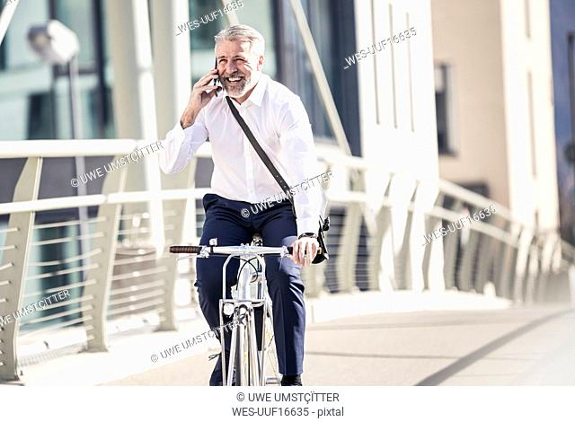 Happy mature businessman talking on cell phone and riding bicycle on a bridge in the city