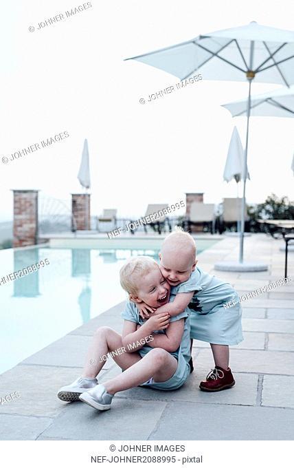 Sisters hugging at swimming-pool