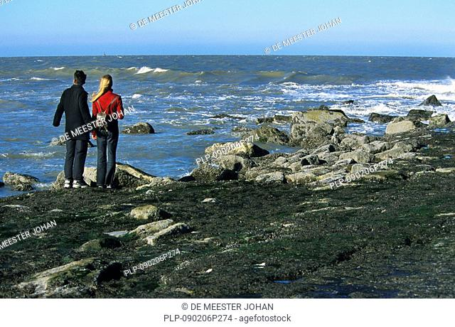 Tourists on breakwater covered in seaweed, Ostend, Belgium