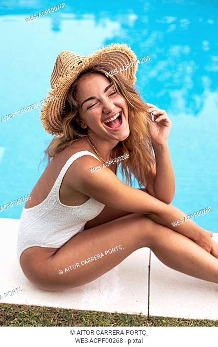 Young girl smiling with straw hat and swimsuit sitting at poolside