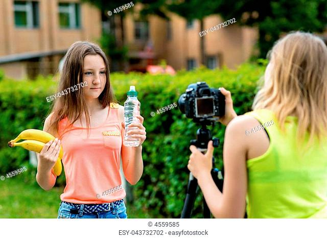 Young girls bloggers, in the summer in city on nature. Record video on the camera. In her hands holds a bottle of water and two bananas
