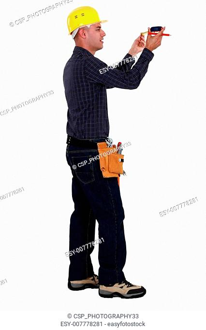A male construction worker taking measures