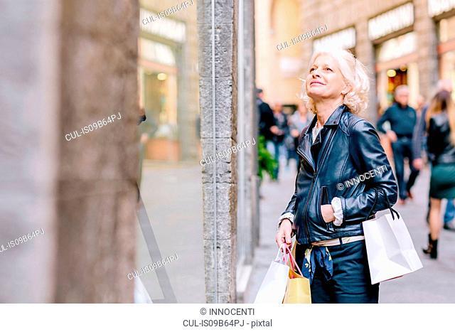 Mature woman window shopping on city street, Siena, Tuscany, Italy