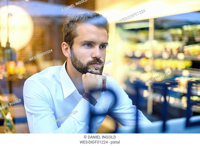 Businessman in a cafe looking through window