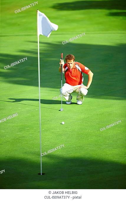 Front view of golfer crouching down in front of golf flag considering strategy