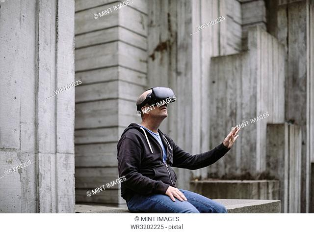 A middle aged man wearing a virtual reality headset