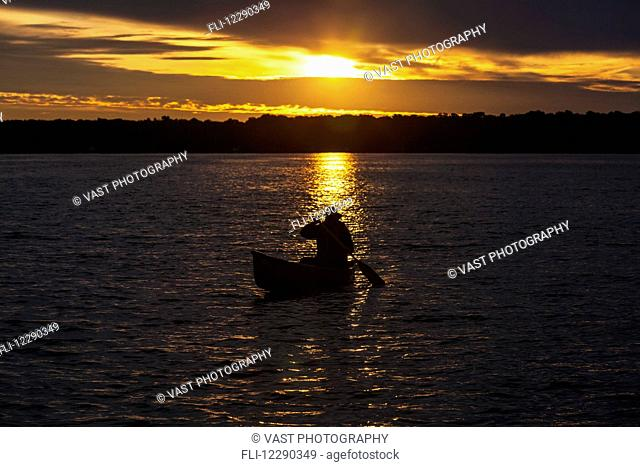 Man paddling canoe at sunrise on Balsam Lake; Ontario, Canada