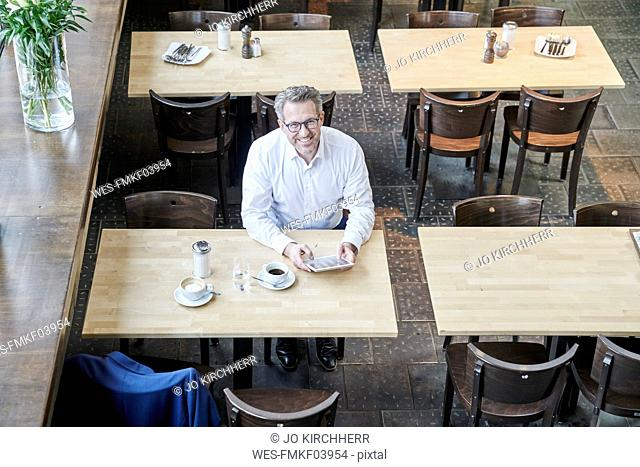 Smiling mature businessman in cafe using tablet