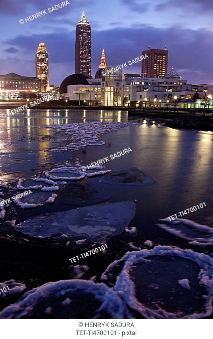 USA, Ohio, Cleveland skyline across frozen lake at sunrise