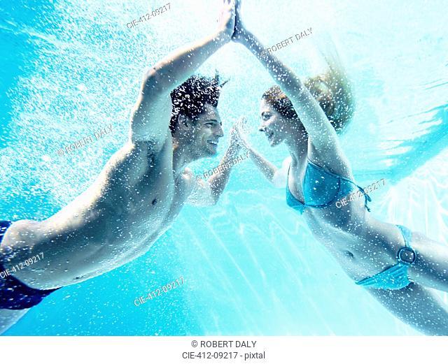 Couple touching hands underwater
